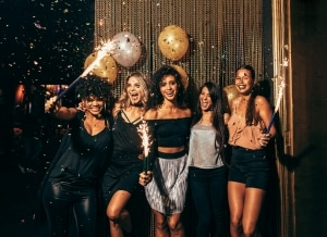 Group of female friends with sparklers partying in nightclub